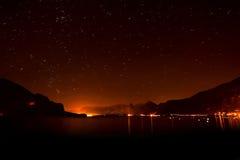 湖的夜视图有光的在天际和满天星斗的天空 免版税库存图片