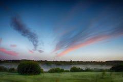 湖的惊人的风景在美丽的蓝天和红色云彩的 免版税库存照片
