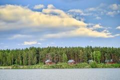 湖的房子在日落的一个杉木森林里 库存图片