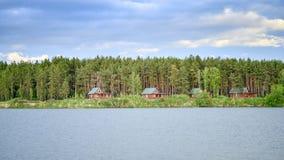 湖的房子在日落的一个杉木森林里 图库摄影