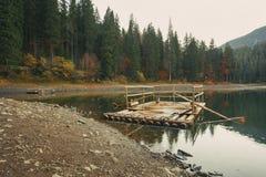 湖的木船坞在秋天森林里 库存图片