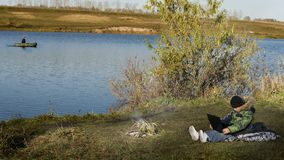 湖的男孩有膝上型计算机的 免版税库存照片