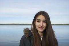 湖的背景的女孩有一个奇怪的表情的 免版税图库摄影