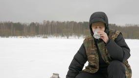 冻湖的年轻人倾吐从热水瓶的热的饮料 非常凉快的地方 股票录像