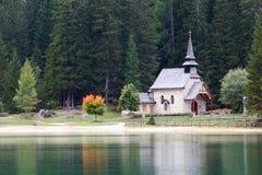 湖的Lago在Dolomiti山的di Braies教会 免版税库存图片