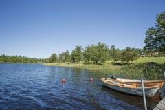 湖看法有在天空蔚蓝背景的岸停放的两条小船的 库存图片