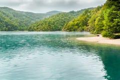 湖看法用与沙子海岛的绿松石水有树的 库存照片