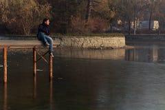 湖码头的年轻男孩 图库摄影