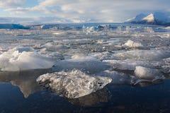 冻湖美好的风景有山背景 免版税库存照片