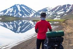 湖背景和降雪的山的愉快的骑自行车的人在冰岛 免版税库存照片
