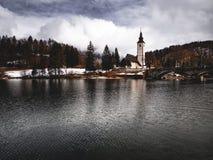 湖边教会有树木繁茂的背景 库存照片