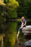 湖边船坞的女孩 免版税库存图片