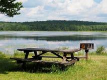 湖边野餐桌和烤肉立场 库存图片