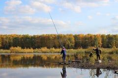 湖边钓鱼的渔夫在一温暖的秋天天 免版税库存图片