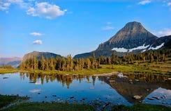 湖风景山和树的看法和反射在镇静水中 免版税库存照片