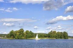 湖风景有白色游艇的在明亮的晴朗的夏日 与白色云彩的蓝天在大湖在特拉凯 图库摄影