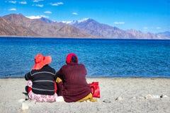 湖8月2018年,Pangong,克什米尔,印度 日间坐在湖pangong旁边的两个游人在大海前面和 库存图片