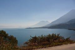 湖Atitlan和火山和路在它附近有看法在圣佩德罗火山 库存照片