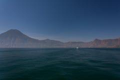 湖Atitlan小船和火山 库存图片