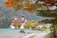 湖Konigssee美好的风景有著名Sankt Bartholomae朝圣教会的由湖边和秋天山在有雾 库存图片