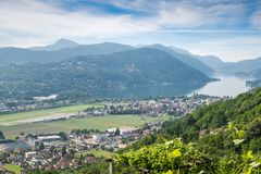 湖lugano瑞士 Agno,湖卢加诺,卢加诺镇的美丽如画的鸟瞰图机场在一个美好的夏日 免版税库存照片