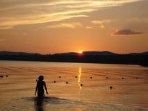 湖raquette日落走的妇女 库存照片