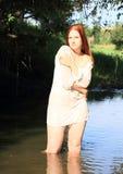 湿女衬衫的女孩在水中 免版税库存照片