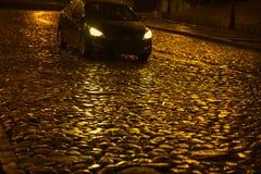湿根据一辆通过的汽车的夜金黄颜色路面 库存图片