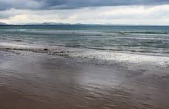 湿海滩作为浪潮后退与在距离的蓝色山脉在风雨如磐的天空-拜伦海湾NSW澳大利亚下 库存照片