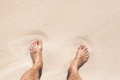 湿男性脚在白色沙子的立场 免版税库存图片
