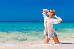 湿白色衬衣的年轻美丽的女孩在海滩 蓝色trop 免版税库存照片