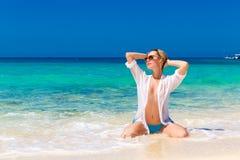 湿白色衬衣的年轻美丽的女孩在海滩 蓝色trop 图库摄影
