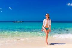 湿白色衬衣的年轻美丽的女孩在海滩 蓝色trop 库存图片