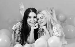 湿背景概念黑暗的友谊鹈鹕的纵向二 白肤金发和深色在微笑的面孔获得乐趣在国内党 在腹部放置的女孩在气球附近 库存照片