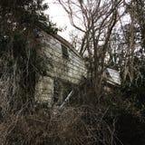 崩溃在本身的被放弃的房子 免版税库存图片