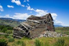 崩溃在蓝天下的被风化的老谷仓 免版税库存照片