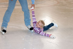 溜冰场的父亲手帮助小逗人喜爱的女孩 库存照片