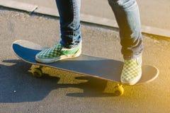 溜冰板者女孩在做在滑板的运动鞋的` s腿一个把戏户外 库存照片