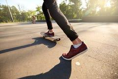 溜冰板者脚特写镜头,当滑冰在冰鞋公园时 在滑板的人骑马 看法,低角度射击 免版税库存图片