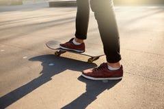 溜冰板者脚特写镜头,当滑冰在冰鞋公园时 在滑板的人骑马 看法,低角度射击 库存照片