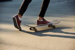 溜冰板者脚特写镜头,当滑冰在冰鞋公园时 在滑板的人骑马 被隔绝的看法,低角度射击 免版税库存图片