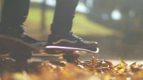 溜冰板者腿踩滑板的utdoors特写镜头  溜冰板者在落叶乘坐滑板在公园 股票录像