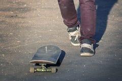 溜冰者在老褴褛运动鞋的一个滑板乘坐 库存图片