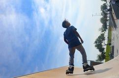 年轻溜冰者在蓝天下似乎几乎象飞行 库存照片