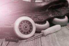 溜冰鞋、轮子和螺丝刀,运动器材修理  免版税库存图片