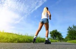 溜冰鞋的十几岁的女孩在夏天 免版税库存照片