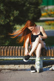 溜冰鞋的妇女坐长凳 免版税库存照片