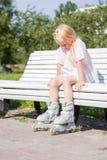 溜冰鞋的逗人喜爱的矮小的白肤金发的女孩坐长凳在公园-休闲、童年、室外游戏和体育概念 免版税库存图片