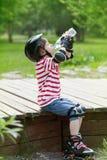 溜冰鞋饮料水的男孩 免版税图库摄影