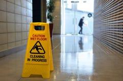 溜滑地板表面警报信号和标志在一个湿地板上 免版税库存图片
